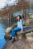 Muchacha adolescente joven que se relaja en el canto rodado grande a lo largo de la orilla del lago, sonriendo Imagen de archivo