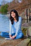 Muchacha adolescente joven que se relaja en el canto rodado grande a lo largo de la orilla del lago, sonriendo Fotografía de archivo
