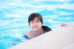Muchacha adolescente joven que se relaja en la piscina, sonriendo en la cámara Fotografía de archivo libre de regalías