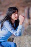 Muchacha adolescente joven que se sienta al aire libre en las rocas que ruegan Imagen de archivo