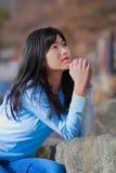 Muchacha adolescente joven que se sienta al aire libre en las rocas que ruegan Imágenes de archivo libres de regalías