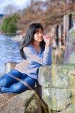 Muchacha adolescente joven que se sienta al aire libre en las rocas que ruegan Fotos de archivo libres de regalías