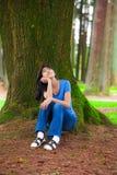 Muchacha adolescente joven que se sienta debajo de los árboles de pino grandes, pensando Foto de archivo