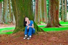 Muchacha adolescente joven que se sienta debajo de los árboles de pino grandes, pensando Imagenes de archivo