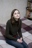 Muchacha adolescente joven que se sienta en cama Imagen de archivo libre de regalías