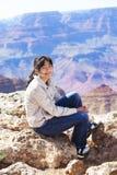 Muchacha adolescente joven que se sienta en el borde rocoso en Grand Canyon Imagen de archivo libre de regalías