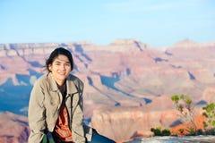 Muchacha adolescente joven que se sienta en el borde rocoso en Grand Canyon Fotos de archivo