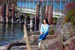 Muchacha adolescente joven que se sienta en los cantos rodados grandes a lo largo de la orilla del lago, mirando hacia fuera sobr Imagenes de archivo