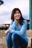 Muchacha adolescente joven que se sienta en pasos de madera al aire libre en día nublado cubierto Imagen de archivo