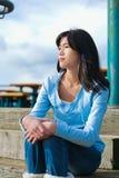 Muchacha adolescente joven que se sienta en pasos de madera al aire libre en día nublado cubierto Fotografía de archivo libre de regalías