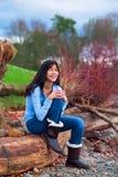 Muchacha adolescente joven que se sienta en registro a lo largo de la playa rocosa del lago Fotos de archivo