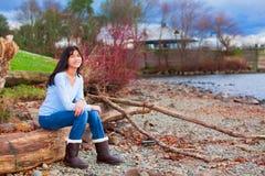 Muchacha adolescente joven que se sienta en registro a lo largo de la playa rocosa del lago Imagenes de archivo