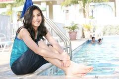 Muchacha adolescente joven que se sienta por la piscina Imagen de archivo libre de regalías