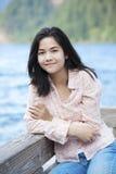 Muchacha adolescente joven que se sienta reservado en el embarcadero del lago Foto de archivo libre de regalías