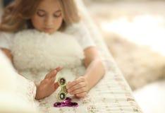 Muchacha adolescente joven que sostiene el juguete popular del hilandero de la persona agitada - el primer se centró en el hiland Foto de archivo