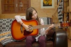 Muchacha adolescente joven que toca la guitarra acústica Imagen de archivo libre de regalías