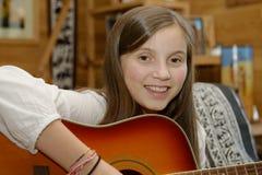 Muchacha adolescente joven que toca la guitarra acústica Imagenes de archivo