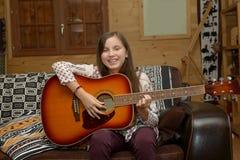 Muchacha adolescente joven que toca la guitarra acústica Fotografía de archivo