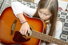 Muchacha adolescente joven que toca la guitarra acústica Foto de archivo libre de regalías