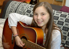 Muchacha adolescente joven que toca la guitarra acústica Fotos de archivo libres de regalías