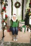 Muchacha adolescente joven sonriente bastante feliz del inconformista delante de adornado para la casa de la Navidad, para el ven Foto de archivo libre de regalías