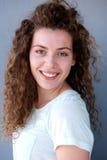 Muchacha adolescente joven sonriente contra la pared gris Imágenes de archivo libres de regalías