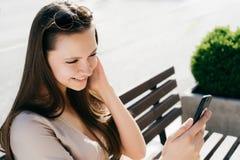 Muchacha adolescente joven sonriente que hace el selfie, mirando a la pantalla móvil MI Imagen de archivo libre de regalías
