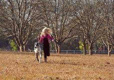 Muchacha adolescente joven y su jugar de funcionamiento del perro en campo abierto Imagen de archivo