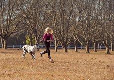 Muchacha adolescente joven y su jugar de funcionamiento del perro en campo abierto Fotos de archivo