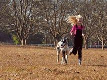 Muchacha adolescente joven y su jugar de funcionamiento del perro en campo abierto Fotografía de archivo