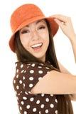 Muchacha adolescente linda americana asiática joven emocionada que lleva el sombrero anaranjado a Imagenes de archivo