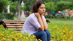 Muchacha adolescente linda bajo tensión que se sienta en banco Imagen de archivo