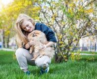 Muchacha adolescente linda con el pelo rubio que juega con su perrito de Pomeranian Imagen de archivo
