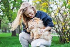 Muchacha adolescente linda con el pelo rubio que juega con su perrito de Pomeranian Imagenes de archivo