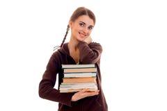 Muchacha adolescente linda con las coletas que sonríe y que sostiene un libro en sus manos Imagen de archivo