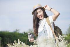 Muchacha adolescente linda del inconformista asiático con la cámara en el jardín de flores blanco Imagenes de archivo