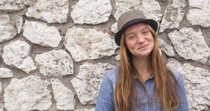 Muchacha adolescente linda en el fondo de la pared de piedra Feliz Fotos de archivo libres de regalías