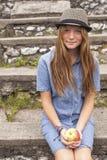 Muchacha adolescente linda en el parque con una manzana en su mano Viajes Imagen de archivo