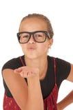 Muchacha adolescente linda en los vidrios de moda que soplan un beso Imagenes de archivo