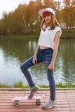 Muchacha adolescente linda en un monopatín cerca del lago Fotos de archivo libres de regalías