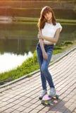 Muchacha adolescente linda en un monopatín en la calle Foto de archivo