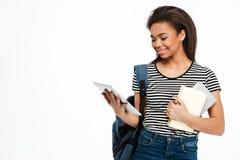 Muchacha adolescente linda feliz con la mochila usando la tableta de la PC Imagen de archivo