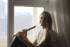 Muchacha adolescente linda joven que juega en la flauta que se sienta en alféizar en casa Fotos de archivo