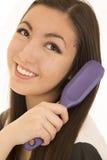 Muchacha adolescente linda que cepilla su sonrisa del pelo oscuro Fotos de archivo libres de regalías