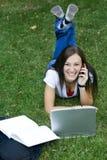 Muchacha adolescente linda que coloca en estudiar de la hierba Foto de archivo