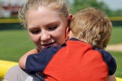 Muchacha adolescente linda que conforta y que detiene al pequeño muchacho Foto de archivo libre de regalías