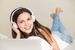 Muchacha adolescente linda que disfruta de nueva música que escucha en línea Imágenes de archivo libres de regalías