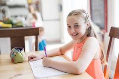Muchacha adolescente linda que hace la preparación en casa Fotos de archivo