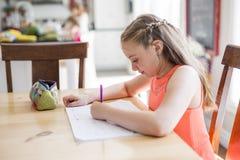Muchacha adolescente linda que hace la preparación en casa Fotografía de archivo libre de regalías
