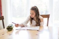 Muchacha adolescente linda que hace la preparación en casa Imagen de archivo